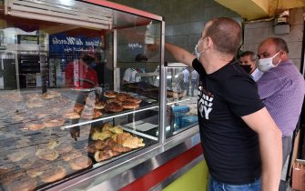 Algerians buy pastries in the capital Algiers on June 7, 2020, after authorities eased some restrictions put in place in a bid to fight the spread of the novel coronavirus. (Photo by RYAD KRAMDI / AFP) (Photo by RYAD KRAMDI/AFP via Getty Images)