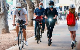 People, wearing protective masks due to the Covid-19 pandemic, ride bicycles and scooters in the Israeli coastal city of Tel Aviv on July 12, 2020. (Photo by JACK GUEZ / AFP) (Photo by JACK GUEZ/AFP via Getty Images)