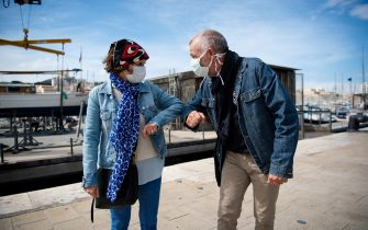 A man and a woman pose as they greet each other with their elbows in the Vieux Port of Marseille southern France, on May 17, 2020, in order to use new social distanciation gesture to salute people as a prophylactic measure against the spread of the Covid-19 disease caused by the novel coronavirus. (Photo by CLEMENT MAHOUDEAU / AFP) (Photo by CLEMENT MAHOUDEAU/AFP via Getty Images)