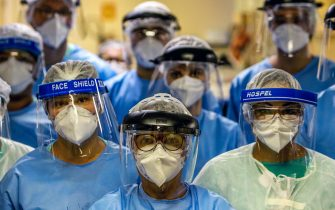 """A group of doctors working with patients infected with the novel coronavirus COVID-19 wear face shields at the Intensive Care Unit of the Hospital de Clinicas in Porto Alegre, Brazil, on April 15, 2020. - With Brazilians increasingly ignoring health officials' warnings to stay home -- encouraged by their far-right president Jair Bolsonaro, who has condemned the """"hysteria"""" over the virus -- predictions for how the pandemic will play out in the hardest-hit country in Latin America are getting dire. (Photo by Silvio AVILA / AFP) (Photo by SILVIO AVILA/AFP via Getty Images)"""