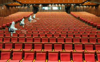 TOPSHOT - This photo taken on May 12, 2020 shows staff members spraying disinfectant at a theatre as it prepares to reopen in Yantai in China's eastern Shandong province. - China's top decision-making body has given the green light for cinemas, entertainment venues and sports facilities nationwide to reopen after several months of closures. (Photo by STR / AFP) / China OUT (Photo by STR/AFP via Getty Images)
