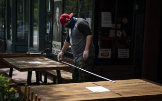 """WASHINGTON, DC - MAY 29: Restaurant employee Paul Sargent measures the distance between tables at the Capitol Lounge in the Capitol Hill neighborhood in Washington, DC on May 29, 2020. Friday was the first day of the city's """"Phase One"""" re-opening following restrictive measures due to the coronavirus pandemic. Restaurants and bars are able to serve a limited number of customers using outdoor spaces, where tables must be spaced six feet apart. (Photo by Drew Angerer/Getty Images)"""