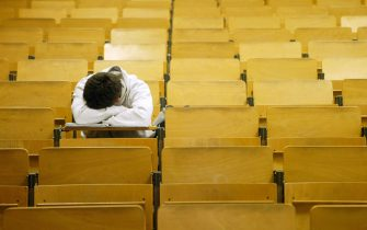 BERLIN, GERMANY - JANUARY 13:  A student naps in a lecture hall at the Freie Universitaet January 13, 2003 in Berlin, Germany. The German university system is facing cuts of EUR 75 million in state funding over the next four years as the German government pushes through financial reforms. German politicians are also deliberating whether to start making students pay for at least a portion of the costs of their university education, though the proposal has met with fierce resitance from students, who went on strike across Germany last month.   (Photo by Sean Gallup/Getty Images)
