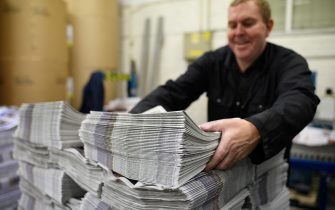 BARNSLEY, ENGLAND - SEPTEMBER 20: A member of the packing team stacks copies of the weekly newspaper as the latest edition is printed at the Barnsley Chronicle press during a nightshift on September 20, 2018 in Barnsley, England. The latest newspaper circulation figures, covering 2017, listed a readership of 19,855 copies per week. Launched in 1858, the Barnsley Chronicle is one of the last privately-owned weekly newspapers in the country, producing each copy in house with their own journalists, design team and full printing press. Owned and operated by the Hewitt family since 1923, it is the largest circulating weekly newspaper in Yorkshire, with profits boosted by off-shoot companies such as military history publishers Pen and Sword and go-kart company Tyke Racing, operating under the Acredula Group. (Photo by Leon Neal/Getty Images)
