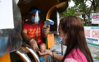 A worker (L) takes the temperature and sprays disinfectant for a passenger on a jeepney in Manila on July 6, 2020, after thousands of jeepneys hit the road again after over three months since they were forced to stop operation amid the COVID-19 coronavirus pandemic. (Photo by Ted ALJIBE / AFP) (Photo by TED ALJIBE/AFP via Getty Images)