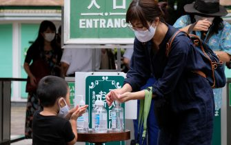Visitors disinfect their hands as a preventive measure against the COVID-19 coronavirus as they enter Toshimaen amusement park in Tokyo on July 13, 2020. (Photo by Kazuhiro NOGI / AFP) (Photo by KAZUHIRO NOGI/AFP via Getty Images)