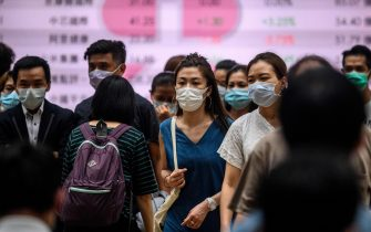 Pedestrians wear face masks as they cross a road in Hong Kong on July 10, 2020, as the city experiences new local outbreaks of the COVID-19 coronavirus. - The finance hub recorded 38 new confirmed cases on July 10, thirty-two of which were locally transmitted. (Photo by Anthony WALLACE / AFP) (Photo by ANTHONY WALLACE/AFP via Getty Images)