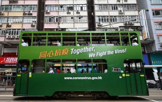 Commuters travel on a tram with a notice that refers to the COVID-19 coronavirus in Hong Kong on July 9, 2020. (Photo by Anthony WALLACE / AFP) (Photo by ANTHONY WALLACE/AFP via Getty Images)