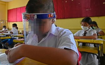 A student wearing a face shield sits in a classroom after their school was reopened in Colombo on July 6, 2020. - Sri Lankan government officially announced all schools to reopen from July 6 for students in Grade 5, 11 and 13 after being closed since March due to lockdown which was imposed as a preventive measure against the spread of the COVID-19 coronavirus. (Photo by LAKRUWAN WANNIARACHCHI / AFP) (Photo by LAKRUWAN WANNIARACHCHI/AFP via Getty Images)