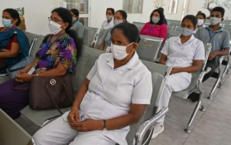 Sri Lankan medical workers wearing facemasks wait for their turn to cast postal ballots for the parliamentary elections, as the officials involved in conducting the polls are allowed to vote via post, in Colombo on July 13, 2020. - The parliamentary elections were to be held on April 25, but were postponed twice before being rescheduled for August. The country has reported 2,605 cases of Covid-19 coronavirus with 11 deaths so far. (Photo by LAKRUWAN WANNIARACHCHI / AFP) (Photo by LAKRUWAN WANNIARACHCHI/AFP via Getty Images)