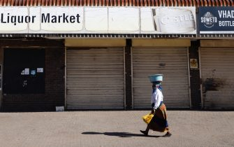 A woman walks past a closed liquor shop in Soweto, on July 13, 2020. - South African President Cyril Ramaphosa on July 12, 2020 re-imposed a night curfew and suspended alcohol sales as COVID-19 coronavirus infections spiked and the health system risked being overwhelmed. (Photo by Michele Spatari / AFP) (Photo by MICHELE SPATARI/AFP via Getty Images)