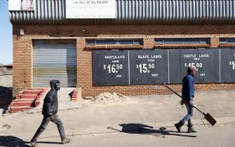 People walk past a closed liquor shop in Soweto, on July 13, 2020. - South African President Cyril Ramaphosa on July 12, 2020 re-imposed a night curfew and suspended alcohol sales as COVID-19 coronavirus infections spiked and the health system risked being overwhelmed. (Photo by Michele Spatari / AFP) (Photo by MICHELE SPATARI/AFP via Getty Images)