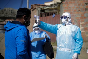 LA PAZ, BOLIVIA - JULY 12: A health worker measures the temperature to a man during an operation to identify COVID-19 cases amid the Coronavirus pandemic on July 12, 2020 in La Paz, Bolivia. According to the World Health Organization, Bolivia has over 47,000 positive cases of COVID-19 and more than 1700 deaths. (Photo by Gaston Brito/Getty Images)