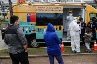 People queue outside a Health Ministry van to be tested for COVID-19 in Santiago, Chile, on July 10, 2020. (Photo by JAVIER TORRES / AFP) (Photo by JAVIER TORRES/AFP via Getty Images)