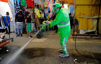 A municipal worker cleans and disinfects a sidewalk in Tepito neighborhood in Mexico City on July 12, 2020, amid the new coronavirus pandemic. (Photo by CLAUDIO CRUZ / AFP) (Photo by CLAUDIO CRUZ/AFP via Getty Images)