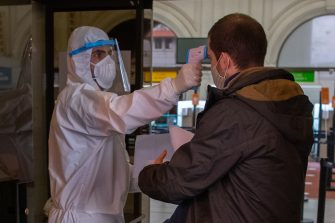 An employee in protective suit checks the temperature of a passenger entering Argentinian ferry service company Buquebus' terminal in the port of Montevideo, on July 10, 2020, amid the new coronavirus pandemic. - Technicians of the Technological Laboratory of Uruguay (LATU) set up a floating laboratory on a ferryboat of Buquebus -the only liner linking the capitals- after the polemic entry to Uruguay of two Argentinian citizens infected with COVID-19 in June. The Uruguayan government of President Luis Lacalle Pou requires since Monday that travellers from abroad have a negative test for the new coronavirus done within 72 hours before the trip and another one seven days after, since flights from Europe were resumed. (Photo by Pablo PORCIUNCULA / AFP) (Photo by PABLO PORCIUNCULA/AFP via Getty Images)