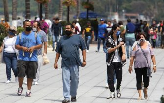 Tourists walk along the Laguna de Chapala boardwalk in Chapala, state of Jalisco, Mexico, after the easing of measures and restrictions imposed to fight the spread of the novel coronavirus, COVID-19, on July 12, 2020. (Photo by Ulises RUIZ / AFP) (Photo by ULISES RUIZ/AFP via Getty Images)
