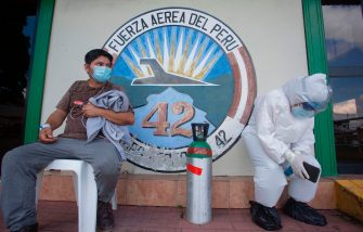 A medical worker (L) showing symptoms of the novel coronavirus COVID-19, waits for an ambulance with a relative wearing a protective suit in Iquitos, in the Amazon Forest in northern Peru, upon arriving on a plane from San Isidro community, on July 11, 2020. - Peru surpassed 320,000 cases of the novel coronavirus on July 11, while around 12,000 COVID-19 patients remain hospitalized and more than 11,600 have died. Peru, with 33 million inhabitants, is the second country in Latin America with the most cases of COVID-19, behind Brazil, and stands fifth in the world. (Photo by Cesar Von BANCELS / AFP) (Photo by CESAR VON BANCELS/AFP via Getty Images)
