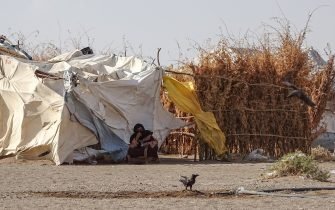 A woman sits outside a tent at a displaced persons camp in the Khokha district of Yemen's western province of Hodeida, on May 6, 2020. - Almost six years of war between the Yemeni government and tenacious Iran-backed Huthi rebels has pushed millions to the brink of famine in the country ill prepared to face the new threat. Squalid camps for internally displaced people like the one in Al-Khokha, outside the Red Sea port city of Hodeida, are ideal breeding grounds for disease, with little chance for proper sanitation or social distancing. (Photo by Khaled ZIAD / AFP) (Photo by KHALED ZIAD/AFP via Getty Images)