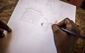 A child illustrates his father's death during a drawing session at the Lazare camp for internally displaced people (IDP) in Kaga Bandoro on May 23, 2019. - In the northern part of the country devastated by the crisis, the International Red Cross has set up a workshop to detect and treat Post Traumatic Stress Disorder through drawing. (Photo by FLORENT VERGNES / AFP)        (Photo credit should read FLORENT VERGNES/AFP via Getty Images)
