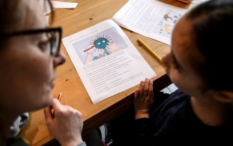 A mother helps her 5-year-old child to do school homeworks on the COVID-19 coronavirus on March 12, 2020 in Manta, near Cuneo, Northwestern Italy, as Italy shut all stores except for pharmacies and food shops in a desperate bid to halt the spread of a coronavirus that has killed 827 in the the country in just over two weeks. (Photo by MARCO BERTORELLO / AFP) (Photo by MARCO BERTORELLO/AFP via Getty Images)