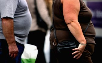 """GLASGOW, UNITED KINGDOM - OCTOBER 10: An overweight person walks through Glasgow city centre on October 10, 2006 in Glasgow, Scotland. According to government health maps published today, people in the north of England lead less healthy lifestyles compared to those in the south. The United Kingdom is also the fattest country in Europe, according to a new study of obesity rates to be released today. The """"Health Profile of England"""" report, compiled from government data, said some 24 percent of people in England, Wales, Scotland and Northern Ireland are obese.  (Photo by Jeff J Mitchell/Getty Images)"""