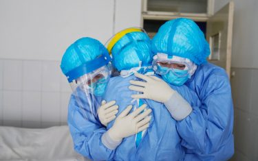 This photo taken on January 28, 2020 shows medical staff members hugging each other in an isolation ward at a hospital in Zouping in China's easter Shandong province. - China faced deepening isolation over its coronavirus epidemic on February 1 as the death toll soared to 259, with the United States leading a growing list of nations to impose extraordinary Chinese travel bans. (Photo by STR / AFP) / China OUT (Photo by STR/AFP via Getty Images)