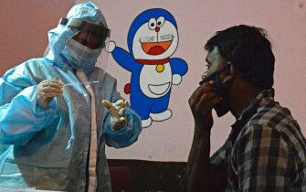 A health worker wearing personal protective equipment (PPE) gear collects a swab sample of a resident at a free testing centre for the COVID-19 coronavirus, at a government primary school in Secunderabad, the twin city of Hyderabad on July 14, 2020. - India has almost 880,000 virus cases and more than 23,000 dead, and experts say the peak is still weeks away. (Photo by NOAH SEELAM / AFP) (Photo by NOAH SEELAM/AFP via Getty Images)