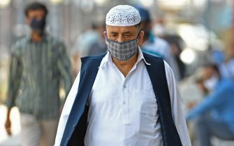 People wearing facemasks walk along the street during a lockdown imposed by authorities after a sudden surge of COVID-19 coronavirus cases, in Srinagar on July 14, 2020. - India has almost 880,000 virus cases and more than 23,000 dead, and experts say the peak is still weeks away. (Photo by TAUSEEF MUSTAFA / AFP) (Photo by TAUSEEF MUSTAFA/AFP via Getty Images)