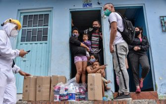 BOGOTA, COLOMBIA - JULY 13: Recidents receive humanitarian aid at their homes in the neighbourhood of Ciudad Bolivar on July 13, 2020 in Bogota, Colombia. While some areas of the city will remain open with restrictions, others will be on strict lockdown. Bogota starts today a zonal rotating system. The city was divided in areas, which will be closed in determined dates, to reduce the circulation of people and hospital occupation. Government also announced economic aid to those in need. (Photo by Guillermo Legaria/Getty Images)