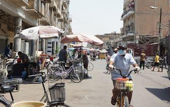 A man wearing a face mask rides a bicycle along the Al-Sadriya Market in the Iraqi capital Baghdad amid the novel coronavirus pandemic crisis on July 9, 2020. (Photo by SABAH ARAR / AFP) (Photo by SABAH ARAR/AFP via Getty Images)