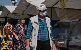 DEDOVSK, RUSSIA - JULY,11 (RUSSIA OUT): Customers in protective masks on the faces seen at a street fair, on July,11,2020 in Dedovsk, 20 km. west of Moscow, Russia. The requirement to wear masks and gloves to combat a spread of the Coronavirus (COVID-19) is still in effect in Moscow. (Photo by Mikhail Svetlov/Getty Images)