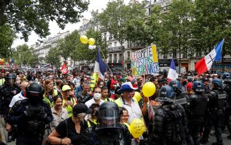 Protesters march surrounded by gendarmes on July 14, 2020, in Paris, during a nationwide day of demonstrations by health workers to demand better work conditions. - Health care workers are protesting in France on the country's National day to demand more for their sector a day after the government and unions signed an agreement giving over eight billion euros in pay rises, with the prime minister admitting the move was overdue in view of the coronavirus pandemic. (Photo by Zakaria ABDELKAFI / AFP) (Photo by ZAKARIA ABDELKAFI/AFP via Getty Images)