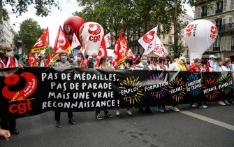 """Protesters hold a banner reading """"No medals, No parade, but real recognition, Employment, training, salary, work conditions, retirement, strenuousness"""" and wave French CGT trade union flags during a demonstration in Paris, on July 14, 2020, as part of a nationwide day of protests by health workers to demand better work conditions. - Health care workers are protesting in France on the country's National day to demand more for their sector a day after the government and unions signed an agreement giving over eight billion euros in pay rises, with the prime minister admitting the move was overdue in view of the coronavirus pandemic. (Photo by Zakaria ABDELKAFI / AFP) (Photo by ZAKARIA ABDELKAFI/AFP via Getty Images)"""