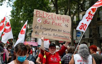 """A protester holds a placard reading """"Polyclinic of Parc, Money for our salaries not for the shareholders"""" during a demonstration in Paris, on July 14, 2020, as part of a nationwide day of protests by health workers to demand better work conditions. - Health care workers are protesting in France on the country's National day to demand more for their sector a day after the government and unions signed an agreement giving over eight billion euros in pay rises, with the prime minister admitting the move was overdue in view of the coronavirus pandemic. (Photo by Zakaria ABDELKAFI / AFP) (Photo by ZAKARIA ABDELKAFI/AFP via Getty Images)"""