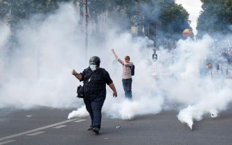 Protesters gesture amid smoke of tear gas during a demonstration in Paris, on July 14, 2020, as part of a nationwide day of protests by health workers to demand better work conditions. - Health care workers are protesting in France on the country's National day to demand more for their sector a day after the government and unions signed an agreement giving over eight billion euros in pay rises, with the prime minister admitting the move was overdue in view of the coronavirus pandemic. (Photo by Zakaria ABDELKAFI / AFP) (Photo by ZAKARIA ABDELKAFI/AFP via Getty Images)