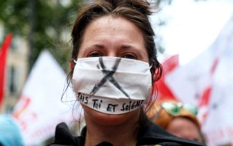 """A protester wears a face mask reading """"Shut up and heal"""" during a demonstration in Paris, on July 14, 2020, as part of a nationwide day of protests by health workers to demand better work conditions. - Health care workers are protesting in France on the country's National day to demand more for their sector a day after the government and unions signed an agreement giving over eight billion euros in pay rises, with the prime minister admitting the move was overdue in view of the coronavirus pandemic. (Photo by Zakaria ABDELKAFI / AFP) (Photo by ZAKARIA ABDELKAFI/AFP via Getty Images)"""