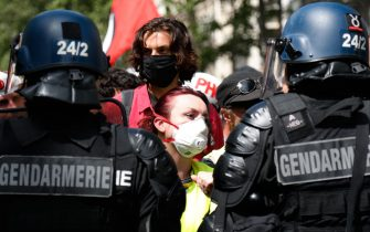 A protester wearing a protective face mask faces French Gendarmes during a demonstration in Paris, on July 14, 2020, as part of a nationwide day of protests by health workers to demand better work conditions. - Health care workers are protesting in France on the country's National day to demand more for their sector a day after the government and unions signed an agreement giving over eight billion euros in pay rises, with the prime minister admitting the move was overdue in view of the coronavirus pandemic. (Photo by Zakaria ABDELKAFI / AFP) (Photo by ZAKARIA ABDELKAFI/AFP via Getty Images)