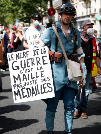 """A protester wearing a costume of a World War I French medic holds a placard reading """"The sinews of war is money, not just medals"""" during a demonstration in Paris, on July 14, 2020, as part of a nationwide day of protests by health workers to demand better work conditions. - Health care workers are protesting in France on the country's National day to demand more for their sector a day after the government and unions signed an agreement giving over eight billion euros in pay rises, with the prime minister admitting the move was overdue in view of the coronavirus pandemic. (Photo by Zakaria ABDELKAFI / AFP) (Photo by ZAKARIA ABDELKAFI/AFP via Getty Images)"""