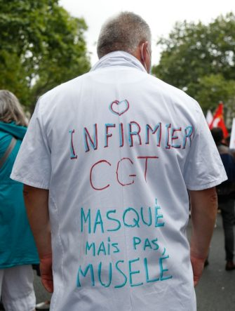 """A protester wears a white coat reading """"CGT nurse, masked not muselled"""" during a  demonstration in Paris, on July 14, 2020, as part of a nationwide day of protests by health workers to demand better work conditions. - Health care workers are protesting in France on the country's National day to demand more for their sector a day after the government and unions signed an agreement giving over eight billion euros in pay rises, with the prime minister admitting the move was overdue in view of the coronavirus pandemic. (Photo by Zakaria ABDELKAFI / AFP) (Photo by ZAKARIA ABDELKAFI/AFP via Getty Images)"""