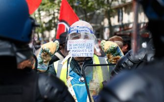 """A protester wearing a yellow vest, oven mitts and a protective visor with a sign reading """"500,000 euros of tableware, that's a lot of masks Brigitte""""  faces gendarmes during a demonstration in Paris, on July 14, 2020, as part of a nationwide day of protests by health workers to demand better work conditions. - Health care workers are protesting in France on the country's National day to demand more for their sector a day after the government and unions signed an agreement giving over eight billion euros in pay rises, with the prime minister admitting the move was overdue in view of the coronavirus pandemic. (Photo by Zakaria ABDELKAFI / AFP) (Photo by ZAKARIA ABDELKAFI/AFP via Getty Images)"""