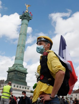 A protester hols a French flag near the July Column on Place de la Bastille, during a demonstration in Paris, on July 14, 2020, as part of a nationwide day of protests by health workers to demand better work conditions. - Health care workers are protesting in France on the country's National day to demand more for their sector a day after the government and unions signed an agreement giving over eight billion euros in pay rises, with the prime minister admitting the move was overdue in view of the coronavirus pandemic. (Photo by Zakaria ABDELKAFI / AFP) (Photo by ZAKARIA ABDELKAFI/AFP via Getty Images)