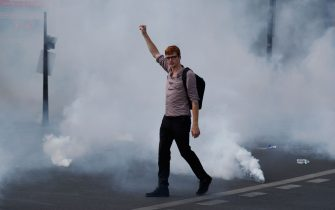 A protester raises a fist during a demonstration in Paris, on July 14, 2020, as part of a nationwide day of protests by health workers to demand better work conditions. - Health care workers are protesting in France on the country's National day to demand more for their sector a day after the government and unions signed an agreement giving over eight billion euros in pay rises, with the prime minister admitting the move was overdue in view of the coronavirus pandemic. (Photo by Zakaria ABDELKAFI / AFP) (Photo by ZAKARIA ABDELKAFI/AFP via Getty Images)