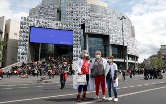 Protesters pose in front of the Opera Bastille bearing portraits of health workers on its facade, at the initiative of the collective #ProtegeTonSoignant to pay tribute to health workers amid the COVID-19 pandemic, during  a demonstration in Paris, on July 14, 2020, as part of a nationwide day of protests by health workers to demand better work conditions. - Health care workers are protesting in France on the country's National day to demand more for their sector a day after the government and unions signed an agreement giving over eight billion euros in pay rises, with the prime minister admitting the move was overdue in view of the coronavirus pandemic. (Photo by Zakaria ABDELKAFI / AFP) (Photo by ZAKARIA ABDELKAFI/AFP via Getty Images)