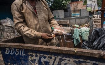 NEW DELHI, INDIA - JULY 14: An Indian ragpicker collects surgical waste items from a dumping site on July 14, 2020  in New Delhi, India.  With over 900,000 confirmed cases and 23,000 deaths, environmental and health experts have warned that India, which is currently the third worst COVID19-affected country, could face further challenges in tackling the impact of the global pandemic if immediate steps are not taken for the proper disposal of masks, gloves, personal protective equipment and other waste materials. (Photo by Yawar Nazir/Getty Images)