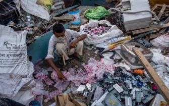 NEW DELHI, INDIA - JULY 14: An Indian ragpicker separates valuable items which he collected from a garbage dump  on July 14, 2020  in New Delhi, India.  With over 900,000 confirmed cases and 23,000 deaths, environmental and health experts have warned that India, which is currently the third worse Covid 19-affected country,  could face further challenges to tackle with the impact of the global pandemic if immediate steps are not taken for the proper disposal of  masks, gloves, personal protective equipment and other waste materials. (Photo by Yawar Nazir/Getty Images)