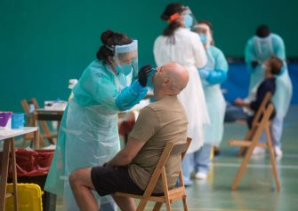 A healthcare worker uses a swab to collect a sample at a temporary testing centre for the novel coronavirus in the Spanish Basque city of Getaria on July 15, 2020. - The novel coronavirus has killed at least 574,278 people since the outbreak emerged in China last December, according to a tally from official sources compiled by AFP at 1900 GMT yesterday. (Photo by ANDER GILLENEA / AFP) (Photo by ANDER GILLENEA/AFP via Getty Images)