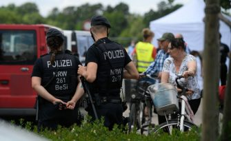 """Police officers stand at the residential homes of employees of the abattoir company Toennies during their quarantine in the district Suerenheide of Verl on June 22, 2020. - The company stopped its production after more than a thousand of employees were tested positive on the novel coronavirus. The German government banned the use of subcontractors in the meat industry after a string of coronavirus infections among mainly foreign slaughterhouse workers sparked alarm already in May 2020. """"It's time to clean up the sector,"""" Labour Minister Hubertus Heil said. From January 1, 2021 abattoirs and meat processing plants will have to directly employ their workers, putting an end to the controversial practice of relying on chains of subcontractors to supply labourers from abroad, often from Bulgaria and Romania. (Photo by Ina FASSBENDER / AFP) (Photo by INA FASSBENDER/AFP via Getty Images)"""