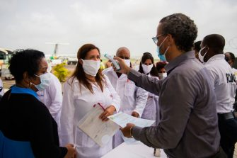 A representative checks the temperatures of  a delegation of Cuban doctors  upon their arrival at the Martinique-Aime-Cesaire airport in Le Lamentin, near Fort-de-France, on the French Caribbean island of Martinique on June 26, 2020, as part of a medical assistance programme amid the COVID-19 pandemic, caused by the novel coronavirus. - A group of 15 Cuban doctors arrived for a three-month mission in Martinique to aid the island's health workers strained by the coronavirus pandemic with a variety of medical work. (Photo by Lionel CHAMOISEAU / AFP) (Photo by LIONEL CHAMOISEAU/AFP via Getty Images)