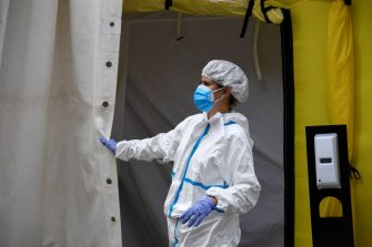 A healthcare workers wearing protective gear waits outside a field hospital set up for coronavirus cases outside the CAP Prat de la Riba primary care centre in Lerida (Lleida) on July 13, 2020. - A local court suspended a home confinement order imposed on more than 200,000 people in the Spanish region of Catalonia after an upsurge in virus cases. Catalonia officials ordered the home confinement on the city of Lerida and its surrounding areas a week after the zone had been placed under less strict lockdown. (Photo by Pau BARRENA / AFP) (Photo by PAU BARRENA/AFP via Getty Images)